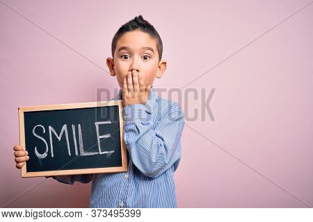 Young little boy kid showing blackboard with smile word as happy message over pink background cover mouth with hand shocked with shame for mistake, expression of fear, scared in silence.