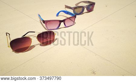 Three Specs Placed On Dry Sand On Beach National Sunglasses Day