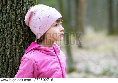 Portrait Of Young Pretty Child Girl Wearing Pink Jacket And Cap Leaning To A Tree In Forest Enjoying
