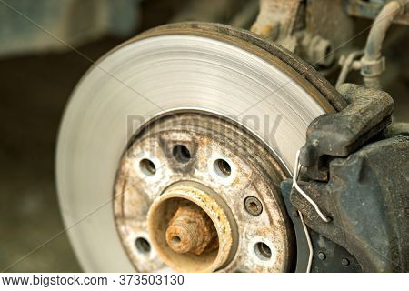 Closeup Of Braking Disc Of The Vehicle With Brake Caliper For Repair In Process Of New Tire Replacem