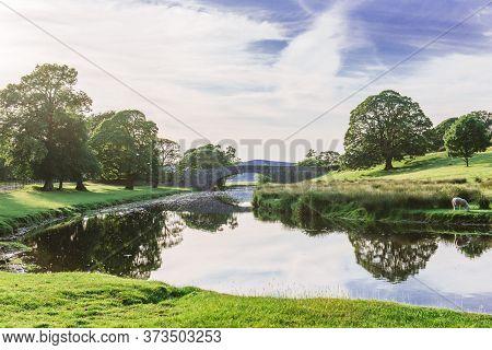 Bridge In Dallam Park, Milnthorpe, Cumbria Passing Over The River Bela On A Sunny Evening