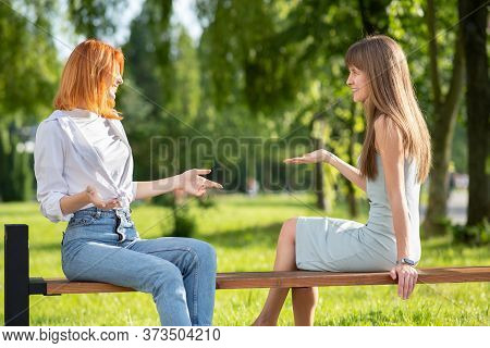 Two Young Women Friends Sitting On A Bench In Summer Park And Talking Having An Argument.