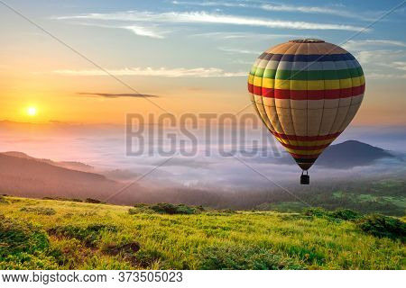 Big Hot Air Baloon Over Idyllic Landscape With Green Grass Covered Morning Mountains With Distant Pe