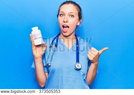 Young beautiful blonde woman wearing doctor uniform holding pills pointing thumb up to the side smiling happy with open mouth