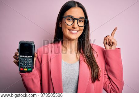 Young beautiful brunette woman holding dataphone paying with credit card to finance surprised with an idea or question pointing finger with happy face, number one