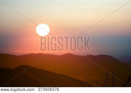 Beautiful Sunset On Top Of Wong Phra Jun Mountain And Silhouette Birds Flying On Red Sky