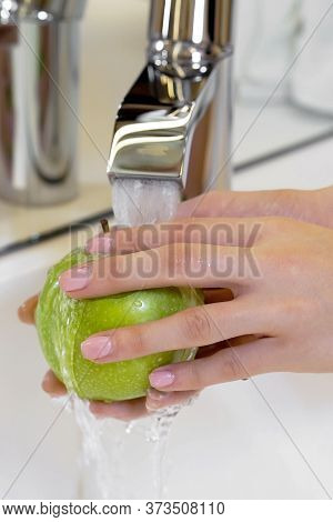 Female Hands Wash Green Apple Under The Tap. Cook Woman Washes A Bunch Of Green Apple Under The Wate