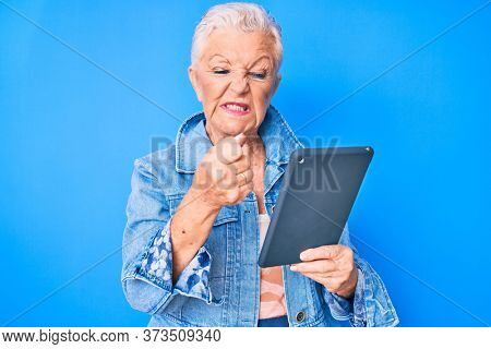 Senior beautiful woman with blue eyes and grey hair using touchpad device annoyed and frustrated shouting with anger, yelling crazy with anger and hand raised