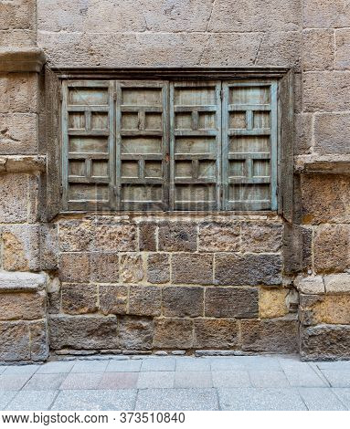 Exterior Shot Of Weathered Stone Bricks Wall And Green Grunge Closed Shuttered Window On Abandoned D