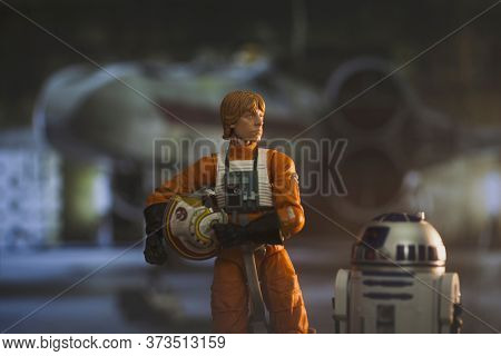 JUNE 23 2020: Scene from Star Wars with Luke Skywalker and droid R2D2 ready to board his X Wing star fighter - Hasbro action figure