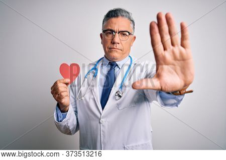 Middle age handsome grey-haired doctor man holding heart of red paper with open hand doing stop sign with serious and confident expression, defense gesture