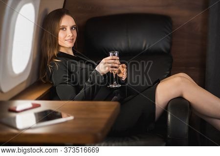 Happy Caucasian Young Woman In Black Dress Relaxing During Flight In Private Jet, Lying On Seat With