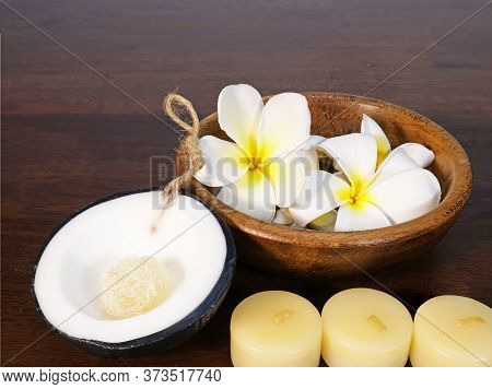 White Tropical Flowers In A Teak Wood Bowl, A Piece Of Coconut Shape Spa Soap And Three White Candle