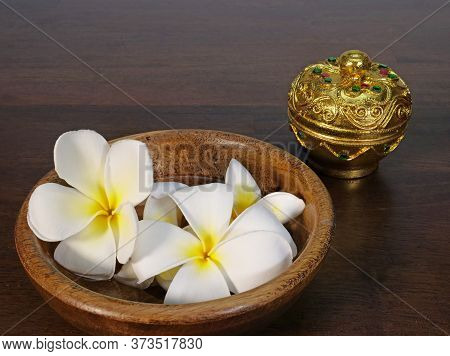 White Tropical Flowers N A Brown Teak Wood Bowl And A Gold Color Piece Of Lacquer Ware On Dark Natur