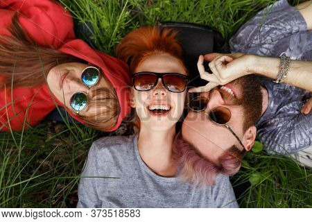 Top View Of A Happy Hipster Youngsters People In Sunglasses, Lying Down On A Green Grass, Wear Sungl