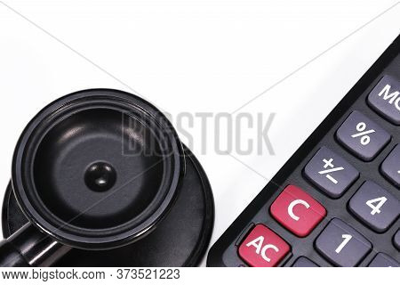 A Black Cardiology Stethoscope And A Medicine Dosage Calculator, Isolated  On White Background