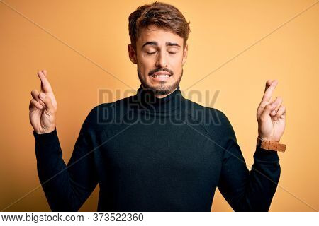Young handsome man with beard wearing turtleneck sweater standing over yellow background gesturing finger crossed smiling with hope and eyes closed. Luck and superstitious concept.