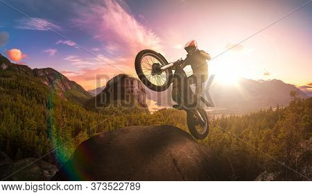 Extreme Adventure Man Motorcycle Trials On Top Of A Rock. Dramatic Mountain Sunset Composite. Landsc
