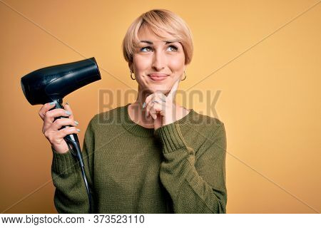 Young blonde woman with short hair drying her hair using hairdryer over yellow background serious face thinking about question, very confused idea