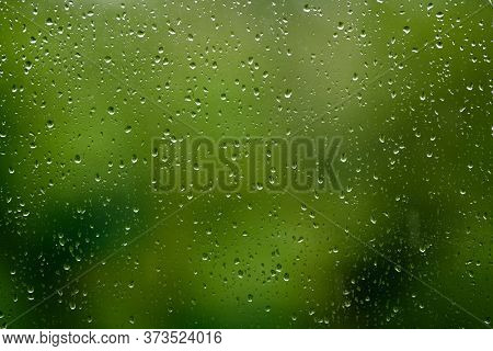 Water droplets on glass over green blurred background. Rainy weather concept