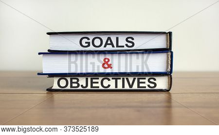 Books With Text 'goals And Objectives' On Beautiful Wooden Table. White Background. Business Concept