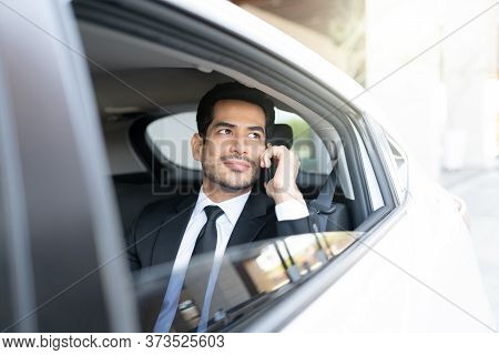 Confident Hispanic Businessman Talking On Mobile Phone While Traveling In Taxi