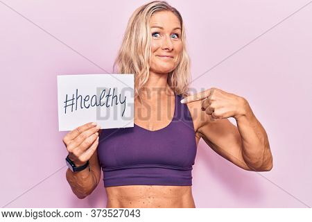 Middle age caucasian blonde woman wearing sportswear holding healthy banner pointing finger to one self smiling happy and proud
