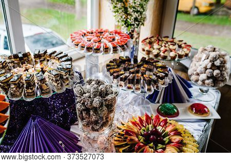 Cupcakes With Cream And Strawberries. Cake, Pie, Fruit Cakes, Muffins, Nuts On A Glass Surface On Th
