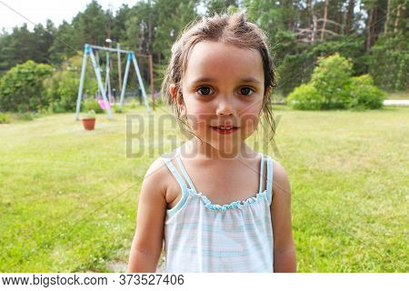 A Child Plays In The Summer On The Playground. A Child Pours Water Into A Children's Pool. The Child