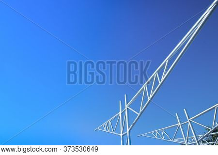 An Image Of Unfinished Metal Trusses Against Bright Blue Sky.
