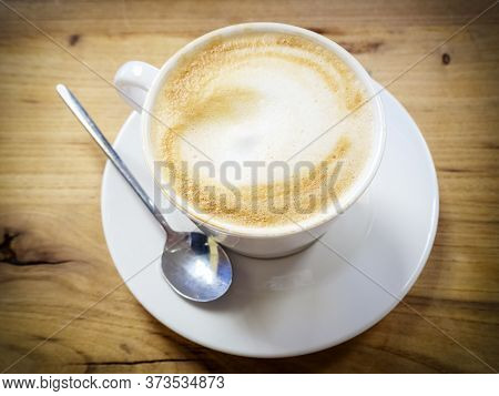 A White Cup With A Cappuccino With Froth Is On A Saucer On A Wooden Surface