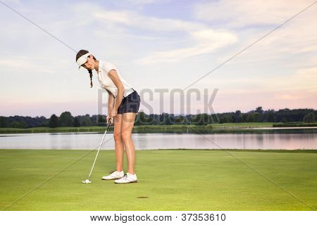 Smiling woman golf player putting on green with lake in background.