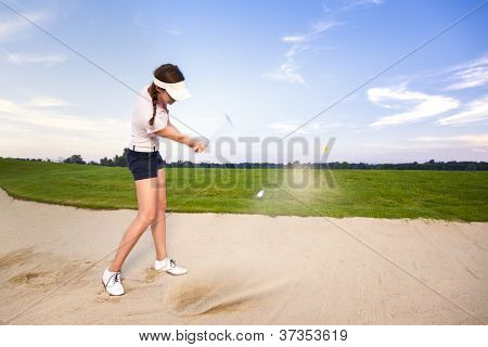 Young woman golfer chipping golf ball out of sand trap onto green with sand wedge and sand caught in motion.