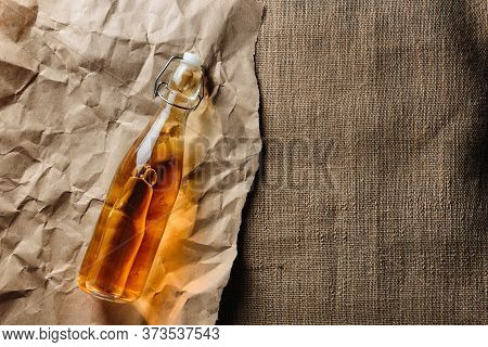 A Bottle Of Homemade Cider Lies On Kraft Paper And Burlap With Copy Space.