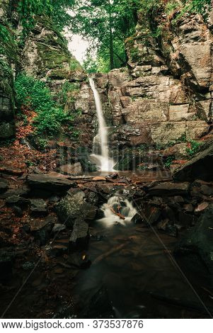 Beautiful View Of Moody And Dramatic Waterfall With Big Rocks And Stones On Foreground In Forest. Da