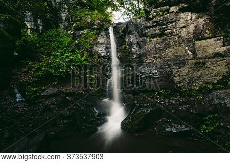 Beautiful View Of Moody And Dramatic Waterfall With Big Rocks And Stones On Foreground In Forest. Sm