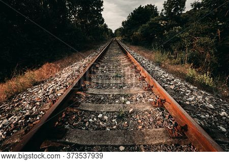 Urbex Photo Of Abandoned, Old And Damaged Train Rails In Country Landscape With Blue Cloudy Sky On B