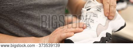 Close-up Of Persons Hands Holding Stylish White Sneakers. Male Wearing Grey Shirt. Man Choosing Shoe