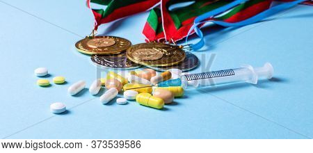 On A Blue Background, Medals, Syringe, Pills. Doping In Sports. Medical And Sports Concept