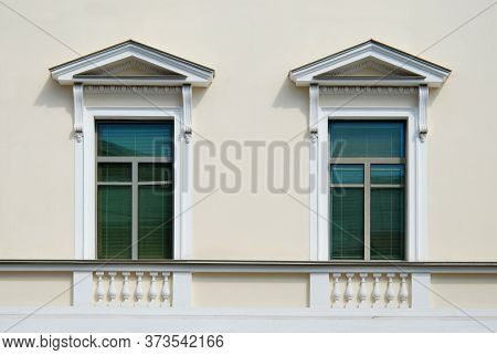 Fine Windows Decorated With Porticos And Balusters