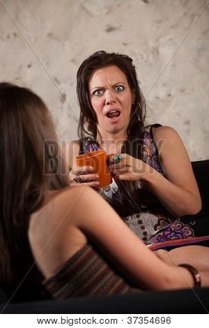 Shocked woman drinking coffee and sitting with friend poster