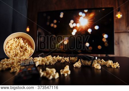 Craft Bowl Of Popcorn On The Dark Table And Tv Remote Control With Tv Set.
