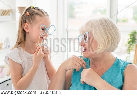 Cute granddaughter and granny holding glasses and lips on sticks in bright room
