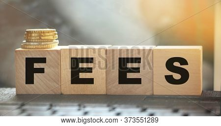 Coin Stack And Wooden Blocks With The Fee Text. Fee Finance And Money Concept