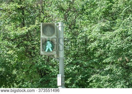 Traffic Light For Pedestrians With A Burning Green Signal In The Form Of A Human Figure On A Backgro