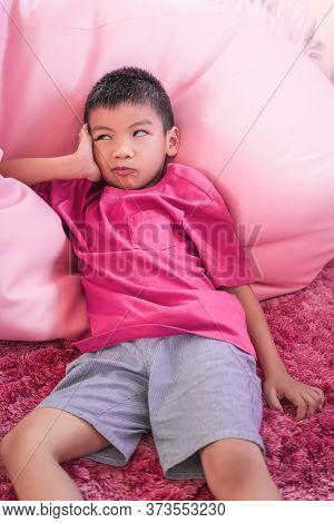 Asian Boy Laying Down Relaxing On A Pink Sofa Bed. With Boredom Unhappy Face.
