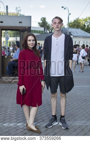 Moscow, Russia - 26.06.2020, Girl In A Red Dress. Man In A White T-shirt, Black Cardigan And Short S