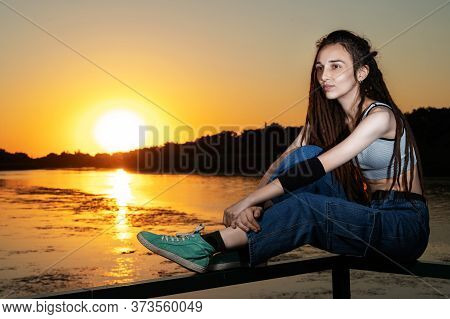 Girl With Dreadlocks Sits On The Railing Of The Bridge On The River Bank At Sunset