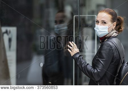 Sad Woman At The Entrance To A Closed Clothing Store In A Shopping Center In A Mask On Her Face. Clo
