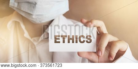 Ethics Word On Card In Hands Of Medical Doctor. Healthcare Confirencial Privacy Concept